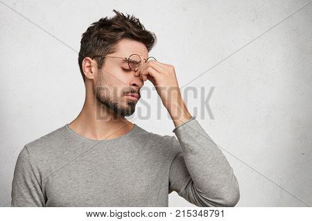 Tired Bearded Male Student Or Office Worker Has Sleepy Expression, Rubbes Nose Because Of Weariness,