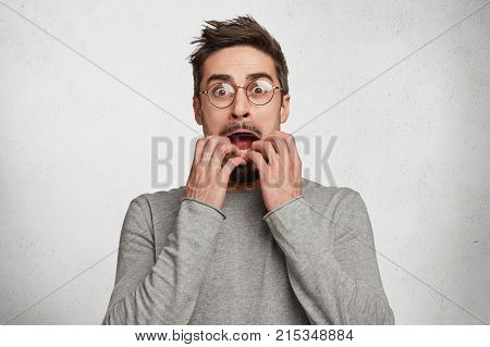 Indoor Shot Of Horrified Frightened Hipster Guy Stares Through Spectacles, Gestures Actively And Ner