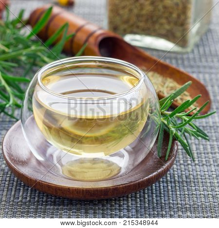 Herbal rosemary tea in a glass cup on oriental background square format