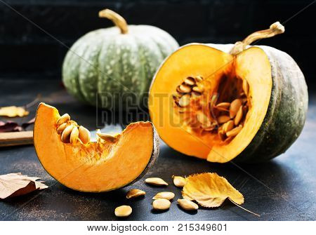 raw pampkin and dry leaves on a table, stock photo