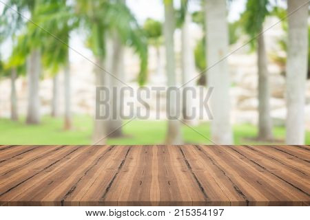 Wood table top on palm tree blurred background for montage your products