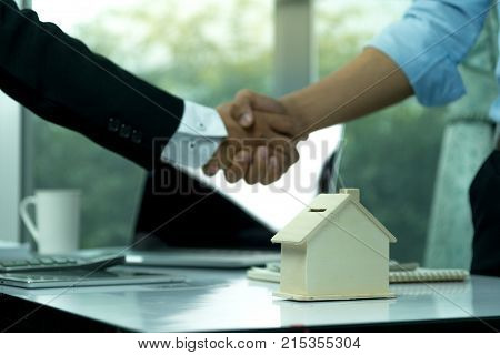 Estate Agent Sitting In A Desk Shaking Hands With Customers After Signing A Home Purchase Contract.