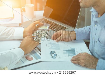 Two Business People Who Use A Calculator With Financial Concepts, Spreadsheet Data, Business People