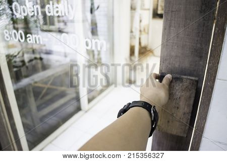 Woman hand opening shop door stock photo