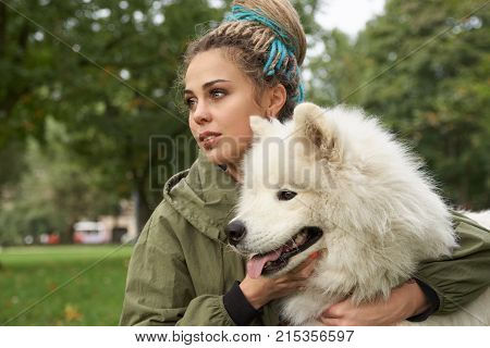 a young woman in a green coat and with dreadlocks on her head resting with her Samoyed dog in the park