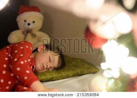 Beautiful boy sleeps on the bed in Christmas night. Child sleeping under a Christmas tree