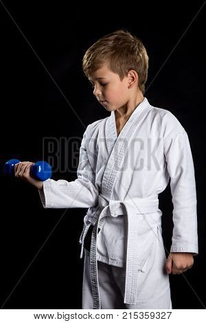 Warm-up before karate. Karate kid in white kimono with a blue dumbbell in the right hand.
