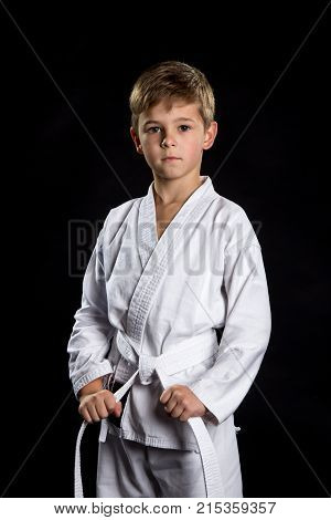 Karate fighter holding his belt. Serious kid in brand new kimono in the front position on the black background.
