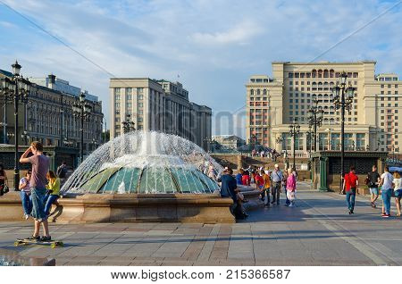 MOSCOW RUSSIA - JULY 23 2016: Unknown people rest on Manezhnaya square. Four Seasons Hotel Moscow 5* (formerly - Moscow Hotel) and building of State Duma