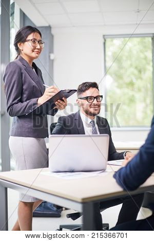 Business partners discussing details of mutually beneficial cooperation while gathered together at spacious meeting room, pretty Asian assistant manager taking necessary notes