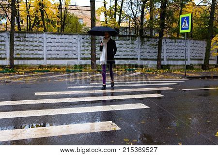 The girl crosses the road on the pedestrian crossing. Autumn.