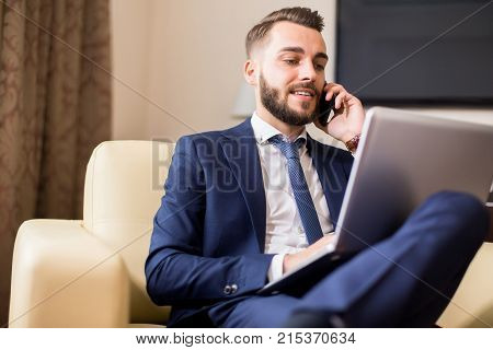 Portrait of handsome young entrepreneur speaking by phone and using laptop while working in comfortable hotel room or office