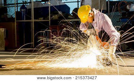 worker uses grinding cut metal focus on flash light line of sharp sparkin low light