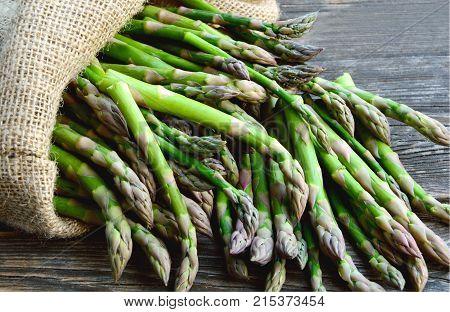 Asparagus or garden asparagus in sack bag on wooden floor