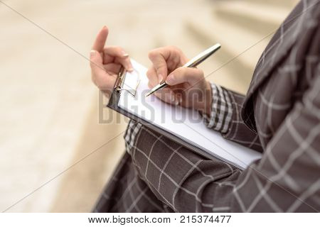 Woman writes something on paper starts to write a letter a document signs papers using a pen. Person sign document write on paper using pen.