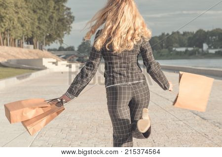 back view of a woman jumping with shopping bags. Girl in a the pantsuit runs away with paper bags in their hands.