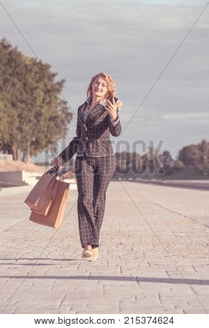 Vertical orange tonted shot of a happy beautiful blond woman with braces running with paper bags and phone in hand along the promenade