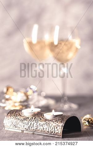 Vertical toned shot of candles in metal candlestick on the background of two wine glasses in blur.