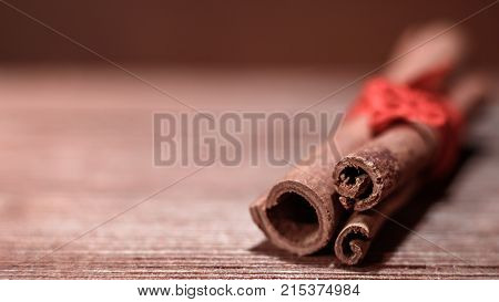 Horizontal shot of cinnamon sticks tied with red ribbon closeup on wooden background blur. Copy space.
