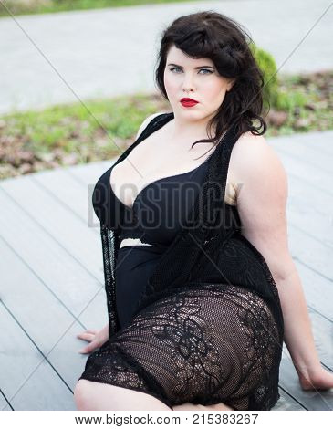 Young beautiful busty curvy plus size model with big breast in black bra and lace cape xxl woman professional makeup and hairstyle sitting outdoors
