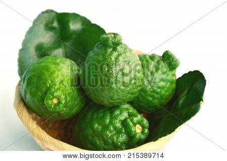 makrut lime or kaffir lime (Citrus hystrix) in basket on white background