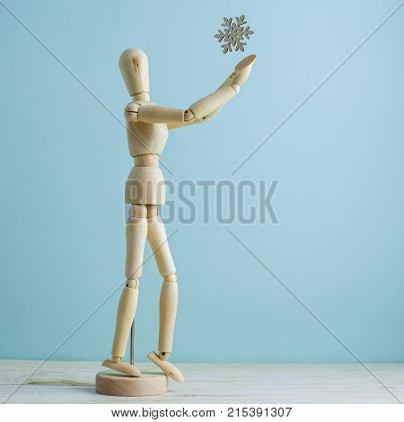 Minimal winter concept. Wooden manikin is trying to catch snowflake