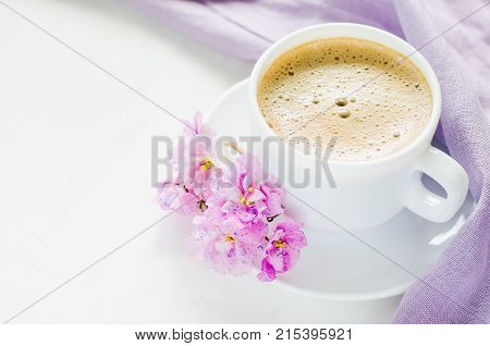 White cup of morning coffee or cappuccino and delicate pink purple lilac flowers. Mother's day concept. Cozy breakfast copy space