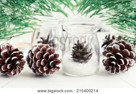 Winter season home decor. Pine cones in glass jar, framed snowy green fir tree boughs.