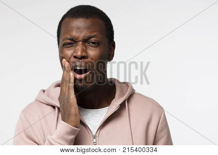 Young Black Man Isolated On Gray Background Wihh Mouth Open, Touching His Face With Expression Of Ho