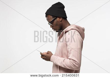 Young Attractive Black Male Looking And At Smartphone With  While Texting His Friend, Using Mobile P