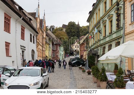 Sighisoara Romania October 08 2017 : Tourists walk on the School Street in the castle of old city. Sighisoara city in Romania