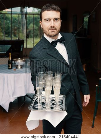 Smiling Cheerful Waiter With Glasses Of Champagne
