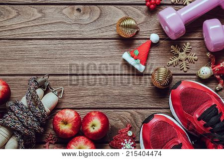 Fitness healthy and active lifestyles love concept dumbbells sport shoes skipping rope or jump rope and apples with Christmas decoration items on wood background. Exercise Fitness and Working Out Merry Christmas and Happy new year concept.