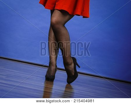 Woman wearing red dress or skirt dark tights and black high heels. Studio shot on blue background. Fashion details.