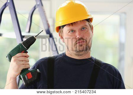 Idiot worker using electric drill portrait. Manual job DIY inspiration improvement fix shop yellow helmet joinery startup idea industrial education profession career concept