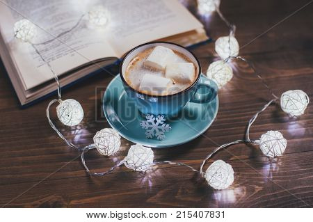 Cozy winter home. Cup of cocoa with marshmallows open book Christmas garland on a wooden table. Kind atmosphere of evening reading.