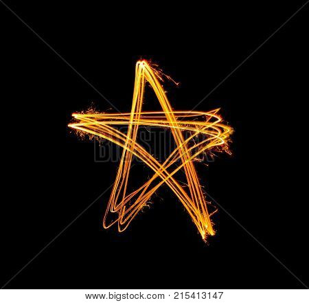 Gold sparkler star shape light painted at night time