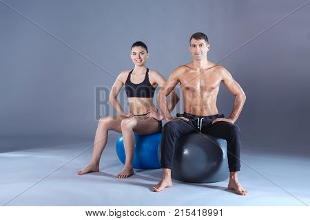 Two smiling people with fitness ball in the gym. Personal fitness instructor. Personal training. Gym workout.