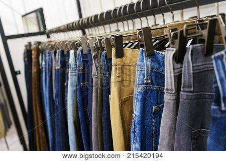 Modern clothes in a shop on a hanger. Jeans of different colors and denim for young people. Jeans of different styles on the hanger in the showroom. Soft focus.