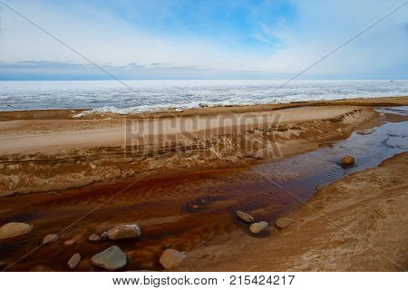 The sandy shores of a shallow, winding creek that flows into the Gulf of Finland, covered with melting ice