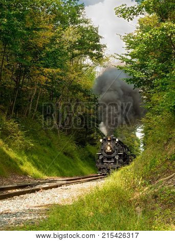 PENINSULA OH - SEPTEMBER 17 2917: The NKP-765 one of the largest steam locomotives still in existence approaches with a full billow of smoke from a narrow pass through woods south of Cleveland.