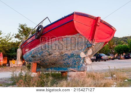 Overgrown in weed old wooden fishing boat dry docked withdrawn to the beach.