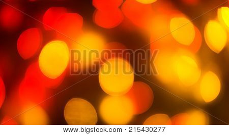 Color light blurred background, red and yellow lights unfocused. Christmas or other holiday decorations, garland illumination bokeh