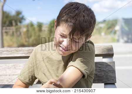 Full body of asian child injured at elbow. Sad boy groaning with a painful gesture.Human health care and problem concept.