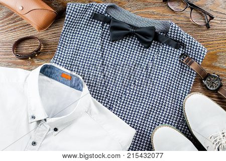 Man's classic clothes outfit flat lay with formal shirt, vest, bowtie, shoes and accessories. Top view