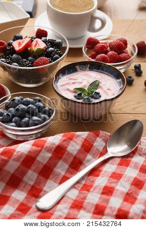 Tasty breakfast with light greek yogurt, fresh strawberries, raspberries, blueberries and blackberries. Low fat morning meals and healthy start of the day. Detox and diet concept