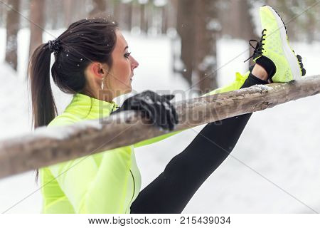 Fit woman athlete doing hamstring leg stretching exercises outdoors in woods. Female sports model exercising outdoor winter park