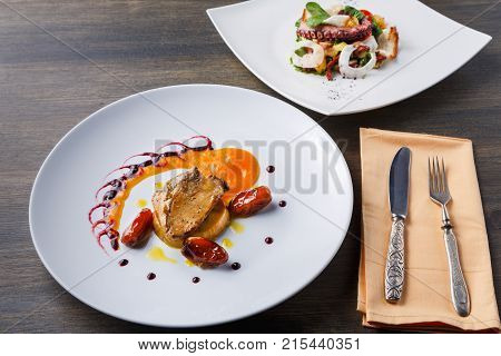 Roasted goose liver with date, apple and fruit and berry sauce painting with cutlery and seafood salad. Creative french cuisine, delicatessen restaurant meal