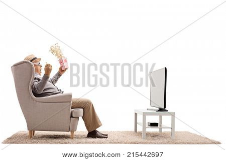 Terrified mature man with popcorn and 3D glasses sitting in an armchair and watching television isolated on white background