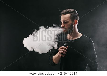 Man with vaping mod exhaling steam at black studio background. Bearded brutal guy in cap e-cigarette to quit tobacco. Vapor and alternative nicotine free smoking concept, copy space